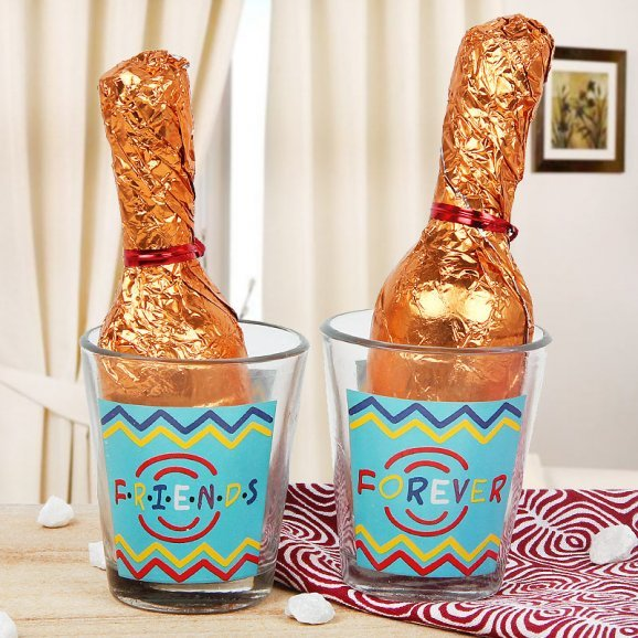 2 tequila glasses with 2 champagne shaped handmade chocolates