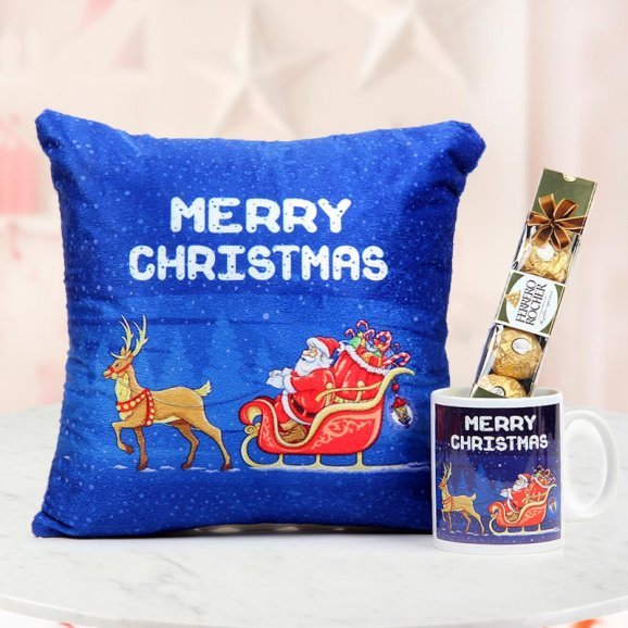 This 12x12 inches fluffy Christmas cushion in bright blue colour with a Merry Christmas Mug and a pack of 4 Ferrero Rocher