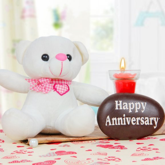 A 6 inches teddy alongwith a glass candle and birthday stone