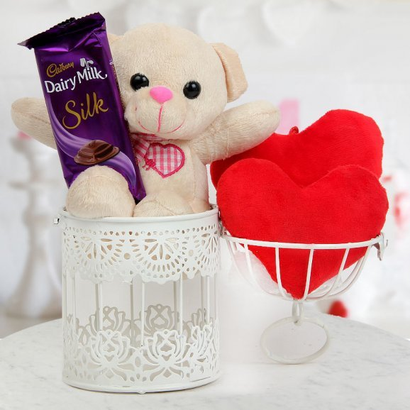 A 3 inch Teddy in a cage with one Dairy Milk Silk and Two tiny heart cushions