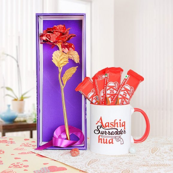 An artificial rose and a mug with 4 kitkats