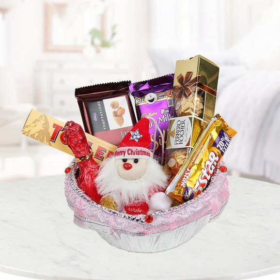 Christmas bowl with a cute little teddy, a pack of 4 Ferrero Rocher, 1 Temptaton, 1 Dairy Milk Silk, one 5-Star, one Champagne shaped Handmade Chocolate, one Toblerone