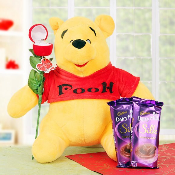 A teddy and chocolates with a ring rose
