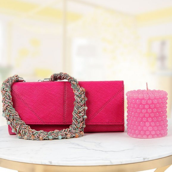 An stylish clutch with matt finish neckpiece and a scented candle