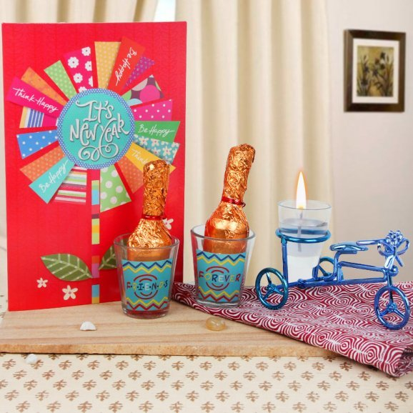 A New Year card with 2 tequila glasses and candle cycle alongwith 2 handmade chocolates