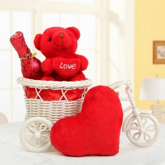 A 3 inch red Teddy in cycle with heart A champagne shaped bottle with chocolates and A heart pillow